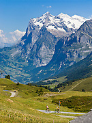 """The Wetterhorn or """"Weather Peak"""" (12,143 feet) rises above bicycle riders ascending Grindelwald Valley near Kleine Scheidegg in the Berner Oberland, Switzerland, the Alps, Europe. Grindelwald can be reached by train (Berner Oberland Bahn) from Interlaken. The Bernese Highlands are the upper part of Bern Canton. UNESCO lists """"Swiss Alps Jungfrau-Aletsch"""" as a World Heritage Area (2001, 2007)."""