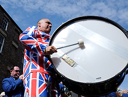© Licensed to London News Pictures. <br /> 10/07/2014. <br /> <br /> Durham, United Kingdom<br /> <br /> Colliery brass bands play with thousands of spectators lining the procession during Durham miners gala.<br /> <br /> The Gala, or Durham Big Meet as it is known locally began in 1871 and today many hundreds of people still meet up in the market place of the city which is the start of the parade. <br /> <br /> The colliery brass bands and banners are followed by those with allegiance to those former colliery villages and they march from there to the cities Racecourse. As they pass the County Hotel on Old Elvet they walk past union leaders, invited guests and local dignitaries who greet the march from the hotel balcony.<br /> <br /> Photo credit : Ian Forsyth/LNP