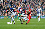 Swansea city's Michu is sent flying by WBA's Gareth McAuley (l) and Claudio Yacob (c) . Barclays Premier league, West Bromwich Albion v Swansea city at the Hawthorns stadium in West Bromwich, England on Saturday 9th March 2013.  pic by  Andrew Orchard, Andrew Orchard sports photography,