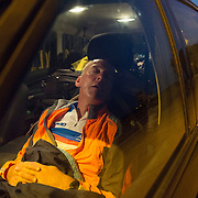 Triathlete Paul Parrish takes a sleep break in the support vehicle  during  the cycle section of his Arch to Arch triathlon attempt in northern France September 16, 2014.