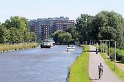 In Leiden fietst een wielrenner op het fietspad langs het  Rijn-Schiekanaal.<br /> <br /> Near Leiden cyclists are riding next to the Rijn-Schiekanaal.