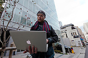 Bitcoin trader, Kolin Burges, from the United Kingdom, checks his computer for news as he protests in front of the abandoned offices of Tokyo-based Bitcoin exchange, Mt. Gox. Shibuya, Tokyo, Japan. Friday February 28th 2014. Mr Burges flew to Japan to personally confront the trading company over his inabilty to withdraw over 260,000 USD worth of the electronic currency. Mt. Gox officially filed for bankruptcy protection on February 28th 2014
