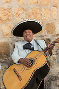 A mariachi musician dressed in traditional charro costume playing a guitarrón November 5, 2013 in Oaxaca, Mexico.