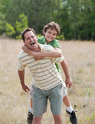 Man Giving A Boy A Piggyback Ride Outdoors In  A Field