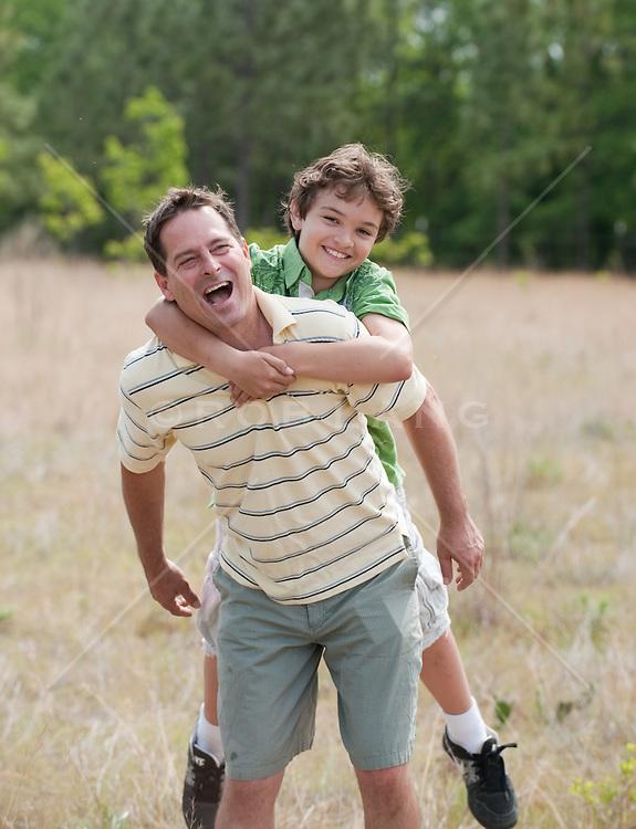 Man Giving A Boy A Piggyback Ride Outdoors In  A Field