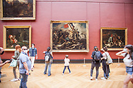 Small crowd with masks watching Liberty lead the people of Delacroix at Louvre museum.