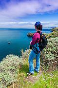 Hiker enjoying the view above Scorpion Cove, Santa Cruz Island, Channel Islands National Park, California USA