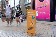 A young man and woman with shopping bags wearing face coverings to prevent the spread of Covid-19 approach a sign welcoming members of the public back to the City Centre on 11th August, 2021 in Leeds, United Kingdom. The British Department of Health has announced that as of Monday, new guidance will mean that even the fully vaccinated will be advised to wear a mask and limit their contact with others if they come into contact with somebody who tests positive for Coronavirus.