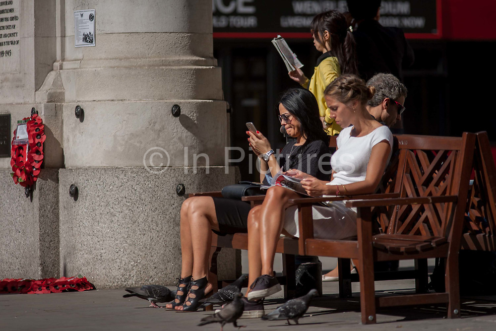 Young women sit reading at Bank Triangle, on 15th August 2016 in the City of London, UK. In warm summer sunshine, Londoners working in the City take a break from the desks of their financial institutions to read magazines and phone messages or social media. Near them is the WW1 war memorial that is located adjacent to the Bank of England.