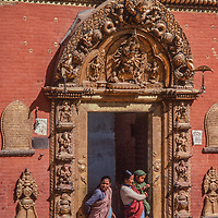 Women and a baby stand in an ornately carved doorway in the Kathmandu Valley, Nepal.