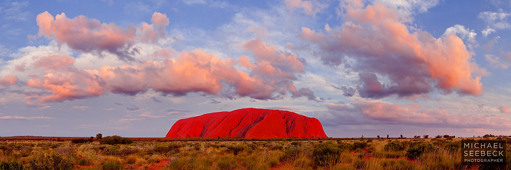 Last rays of sunlight illuminate Uluru as scattered clouds overhead turn orange in the sunset.<br /> <br /> Limited Edition print.