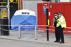 © Licensed to London News Pictures. 06/07/2021. London, UK. Police guard a crime scene at Woolwich New Road in south east London after a 15 year old boy was stabbed to death. Officers were called at 17:23hrs on Monday, 5 July to reports of a stabbing on Woolwich New Road, SE18. Police found a 15-year-old boy suffering from a stab injury. They immediately provided first aid prior to the arrival of the London Ambulance Service. Despite their efforts, he was pronounced dead at the scene. Photo credit: Peter Macdiarmid/LNP