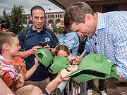 17 AUGUST 2019 - DES MOINES, IOWA: Representative SETH MOULTON (D-MA), right, drops signs farm caps at the Iowa State Fair Saturday. Moulton, a US Marine veteran who served in Iraq, is running to be the Democratic candidate for the US Presidency in 2020 and spent Saturday campaigning at the fair. Iowa traditionally hosts the the first selection event of the presidential election cycle. The Iowa Caucuses will be on Feb. 3, 2020.          PHOTO BY JACK KURTZ