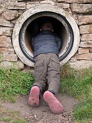 Boy going into playground tunnel