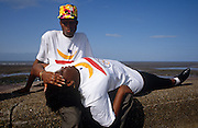A young black couple enjoy each other's company on the sea defence wall while on holiday at Minehead, Somerset.