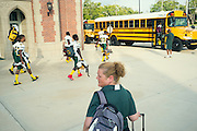 """BIRMINGHAM, AL – SEPTEMBER 11, 2015: Sonya Whitaker (center) waits for the Woodlawn High School football team to board the bus before joining the students. """"I tray to stay back and let him come to me if he gets in trouble. I'm diabetic too."""" As a type 1 diabetic, Quintarius Monroe requires frequent blood sugar testing and supervision when self-administering insulin. When care from qualified personnel at his school in Center Point became unavailable, Monroe was forced to transfer several miles away from his locally zoned school to attend Woodlawn High School. The Americans with Disabilities Act requires schools to provide """"reasonable accommodation"""" for students with medical conditions, but given that most schools no longer retain school nurses, many schools are failing to provide adequate care for their students.<br /> CREDIT: Bob Miller for The New York Times"""