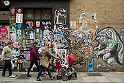 Family walking past paste up street art in Spitalfields in London, England, United Kingdom.