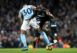 """Manchester City's Nicolas Otamendi (left) and West Ham United's Michail Antonio (right) battle for the ball during the Premier League match at the Etihad Stadium, Manchester. PRESS ASSOCIATION Photo. Picture date: Sunday December 3, 2017. See PA story SOCCER Man City. Photo credit should read: Martin Rickett/PA Wire. RESTRICTIONS: EDITORIAL USE ONLY No use with unauthorised audio, video, data, fixture lists, club/league logos or """"live"""" services. Online in-match use limited to 75 images, no video emulation. No use in betting, games or single club/league/player publications."""