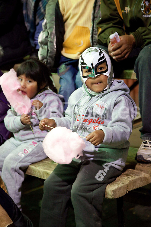 Child in wrestling mask eating candyfloss cotton candy. Lucha Libre wrestling origniated in Mexico, but is popular in other latin Amercian countries, including in La Paz / El Alto, Bolivia. Male and female fighters participate in the theatrical staged fights to an adoring crowd of locals and foreigners alike.