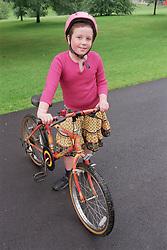 Young girl wearing bike helmet standing next to bike smiling,