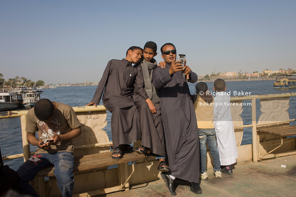 A father takes a selfie with his two boys on the top deck of the state-run ferry across the River Nile at Luxor, Nile Valley, Egypt.