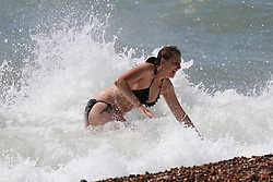 © Licensed to London News Pictures. 15/07/2014. Brighton, UK. a woman playing in the sea on Brighton beach at lunchtime. Temperatures in parts of the south east are expected to hit 30 degrees this week. Photo credit : Hugo Michiels/LNP