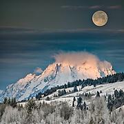 A winter full moon setting behind Mount Moran in the Teton Range.