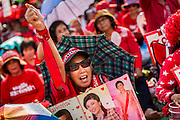 10 MAY 2014 - BANGKOK, THAILAND: A supporter of Yingluck Shinawatra, carrying photos of Yingluck at a Red Shirt rally in Bangkok. Thousands of Thai Red Shirts, members of the United Front for Democracy Against Dictatorship (UDD), members of the ruling Pheu Thai party and supporters of the government of ousted Prime Minister Yingluck Shinawatra are rallying on Aksa Road in the Bangkok suburbs. The government was ousted by a court ruling earlier in the week that deposed Yingluck because the judges said she acted unconstitutionally in a personnel matter early in her administration. Thailand now has no functioning government. Red Shirt leaders said at the rally Saturday that any attempt to impose an unelected government on Thailand could spark a civil war. This is the third consecutive popularly elected UDD supported government ousted by the courts in less than 10 years.    PHOTO BY JACK KURTZ