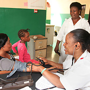 INDIVIDUAL(S) PHOTOGRAPHED: From left to right: Jenifer, unknown, unknown, and Siyanbade Mojisola. LOCATION: Onigbongbo Health Care Center, Lagos, Nigeria. CAPTION: Siyanbade Mojisola takes a patient's blood pressure, accompanied by her 10-year-old daughter, who boosts their mood.