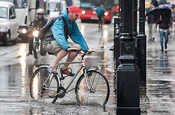 © licensed to London News Pictures. London, UK 11/06/2012. A cyclist rides his bike across a puddle in Regent Street, today (11/06/12). Photo credit: Tolga Akmen/LNP