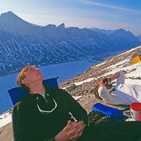 BAFFIN ISLAND, Nunavut, Canada. Jared Ogden & John Catto relax after long day climbing high on huge cliffs of Great Sail Peak. Stewart Valley bkg.