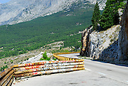 Graffiti covered safety fence, with wooded foothills and Biokovo National Park, part of the Dinaric Alps, in the background. Makarska, Croatia