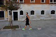 A dog owner and his two miniature pet dogs during a cool evening walk along the waterfront in Dorsoduro, a district in Venice, Italy.