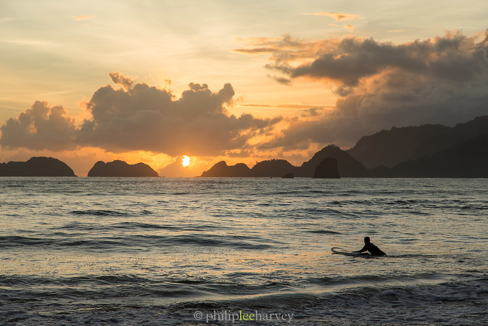 Surfer mounting his board at sunset, Red Island Beach, Red Island, Banyuwangi Regency, East Java, Indonesia, Southeast Asia