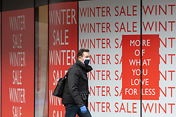 © Licensed to London News Pictures. 06/01/2021. London, UK. Members of the public walk past a closed Peter Jones displaying Winter sales signs in Chelsea, South West London as cases continue to rise dramatically throughout the capital with the UK recording over 60,000 positive tests a day. Yesterday, Prime Minister Boris Johnson plunged England into another lockdown as he ordered schools to close and office workers to work from home in his televised address to the nation. This week, the first person in the world was vaccinated with the Oxford AstraZeneca Covid-19 vaccine with over 500,000 doses made available for high risk groups as the government race to vaccinate 13 million people in seven weeks. Photo credit: Alex Lentati/LNP