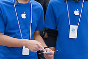 Apple employees check tickets of those waiting in line at the Apple store for the official release of the iphone4S in Ginza, Tokyo, Japan. Friday October 14th 2011. The latest version of the popular iphone was released worldwide on October 14th. Japans flagship Apple store in Ginza was opened at 8am for the 800 people that had been waiting to be the first to purchase the new telephone.