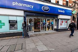 © Licensed to London News Pictures. 04/02/2020. London, UK. Boots chemists in Streatham High Road reopens with what appears to be 3 bullet holes masked by cardboard at the front of the shop and patches of washed street where a knife-wielding terror suspect in a suicide vest was shot dead by undercover police on Sunday 01 February 2020 after stabbing two people in the street. Ministers are trying to bring in legislation to stop extremists being freed early from prison unless agreed by a Parole Board. Photo credit: Alex Lentati/LNP