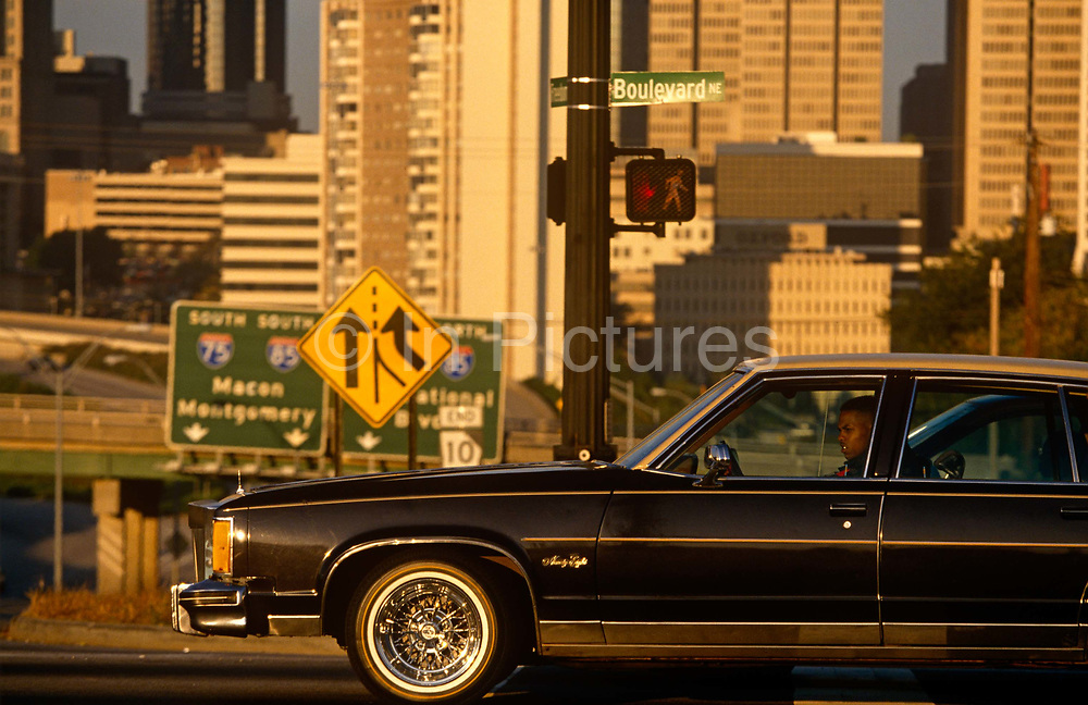 A driver in his gas-guzzling car and in the background, the skyline of downtown Atlanta. Stopped at a traffic light with the cityscape of this American metropolis is the motorist who looks across the road into bright sunshine. We see beyond the long bonnet (hood) of this car the signs for downtown Atlanta and surrounding neighbourhoods such as Macon and Montgomery. According to the 2010 census, Atlanta's population is 420,003 and is a cultural and economic center of the Atlanta metropolitan area, which is home to 5,268,860 people and is the ninth largest in the US.