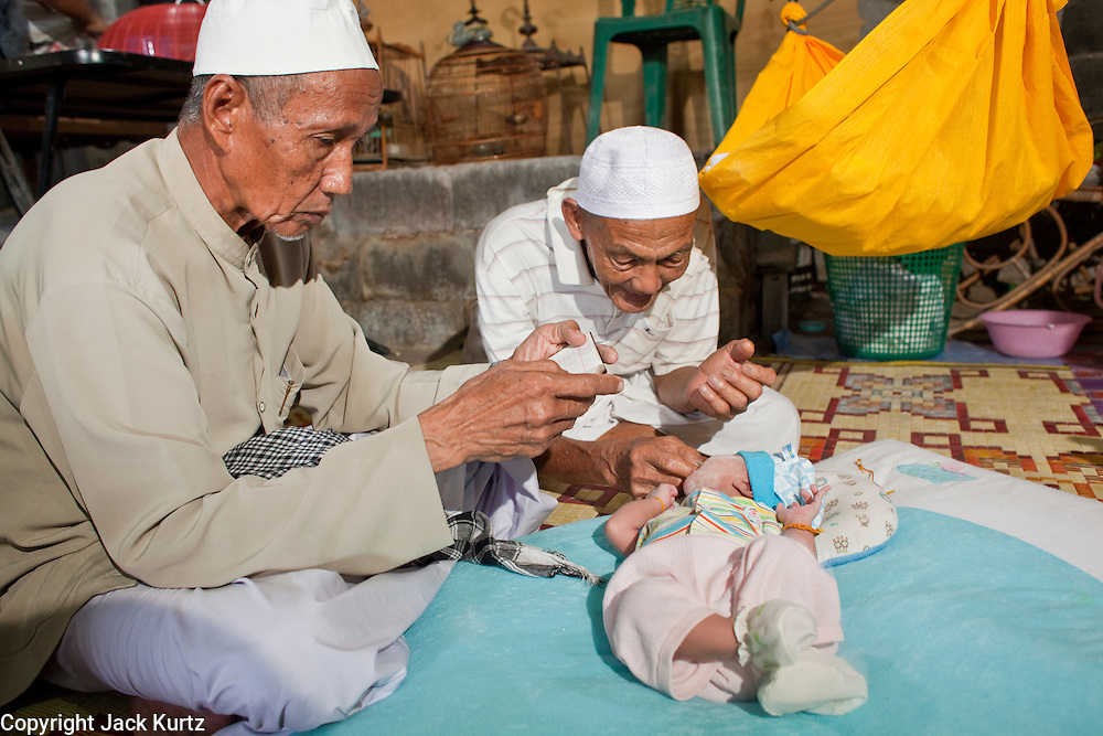 """Sept. 28, 2009 -- TANJONG DATO, THAILAND: The village Imam leads a Tahnik ceremony for newborn baby Nikbukharin while the baby's grandfather holds him in the Muslim village of Tanjong Dato, in the province of Pattani, Thailand. The Tahnik ceremony is a naming ceremony, performed when the baby is one week old. Everybody in the village is Muslim and they say they have no problems, but the roads around the village leading to the provincial capital of Pattani are too dangerous for them to use once it gets dark. Thailand's three southern most provinces; Yala, Pattani and Narathiwat are often called """"restive"""" and a decades long Muslim insurgency has gained traction recently. Nearly 4,000 people have been killed since 2004. The three southern provinces are under emergency control and there are more than 60,000 Thai military, police and paramilitary militia forces trying to keep the peace battling insurgents who favor car bombs and assassination.   Photo by Jack Kurtz / ZUMA Press"""