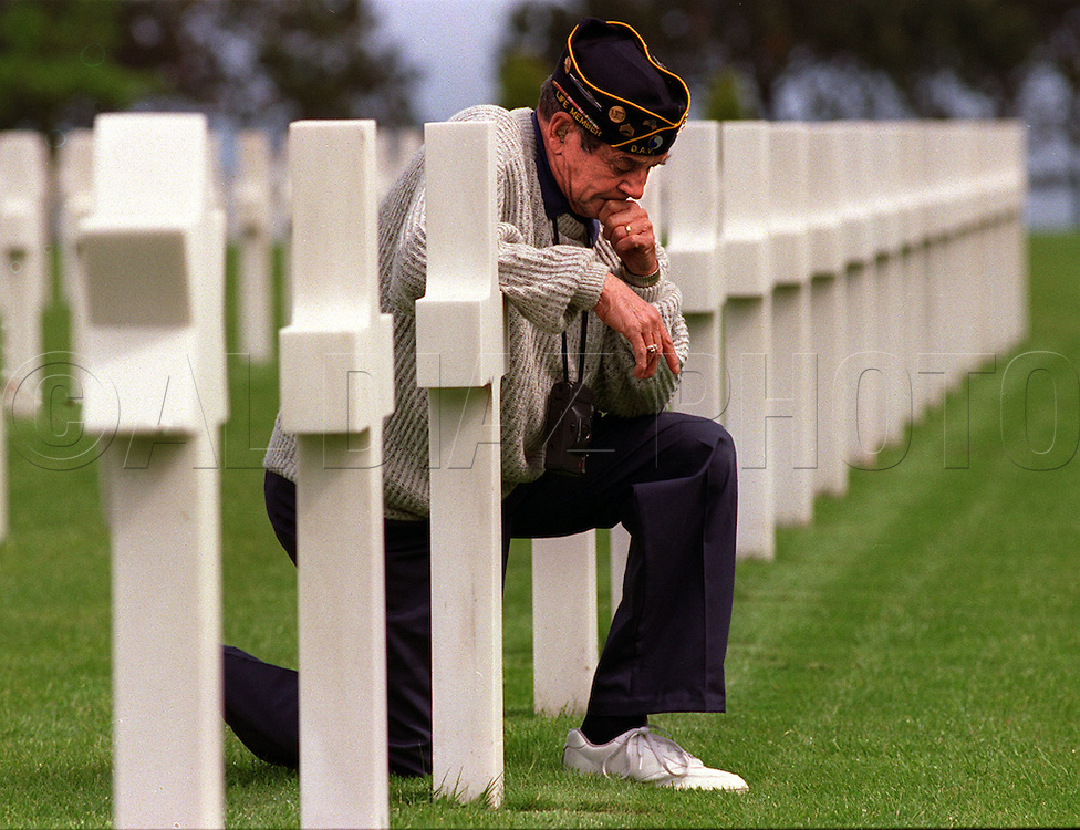 George Treano places his arm on the tombstone of a friend laid to rest at Normandy American Cemetery in Normandy, France on the 50th Anniversary of the allied invasion known as D-Day in 1994. His son Robert said, he's never seen his father cry until that day.