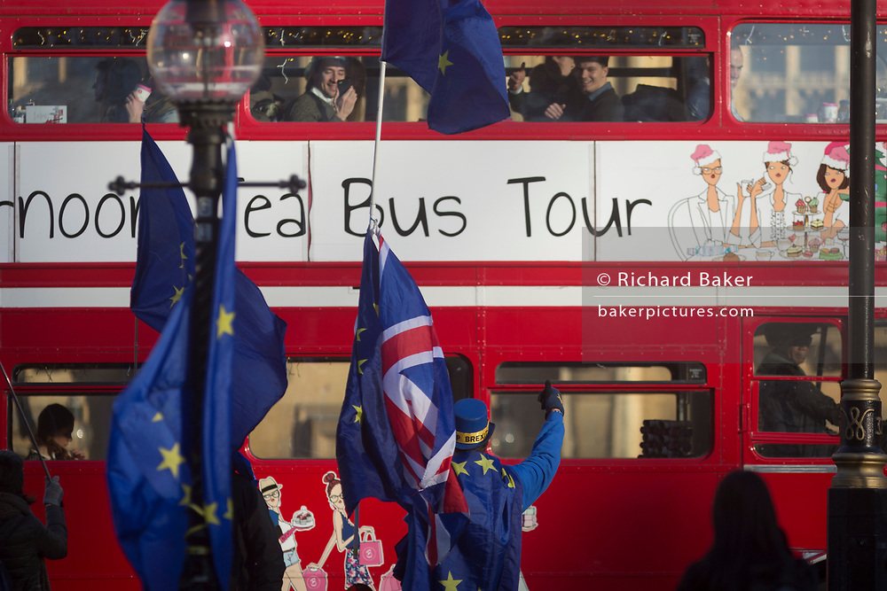 A pro-Europe, anti-Brexit protester gives a thumbs up to tourists passing-by the Houses of Parliament in Westminster, seat of government and power of the United Kingdom during Brexit negotiations with Brussels, on 1st December 2017, in Westminster, London, England.