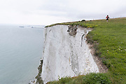 With Dover Dock's harbour wall in the distance, a lone woman walker strides on a clifftop footpath, near the edge of England's iconic White Cliffs, under threat from chalk and soil erosion, on 27th July, in St Margaret's at Cliffe, in Kent, England.