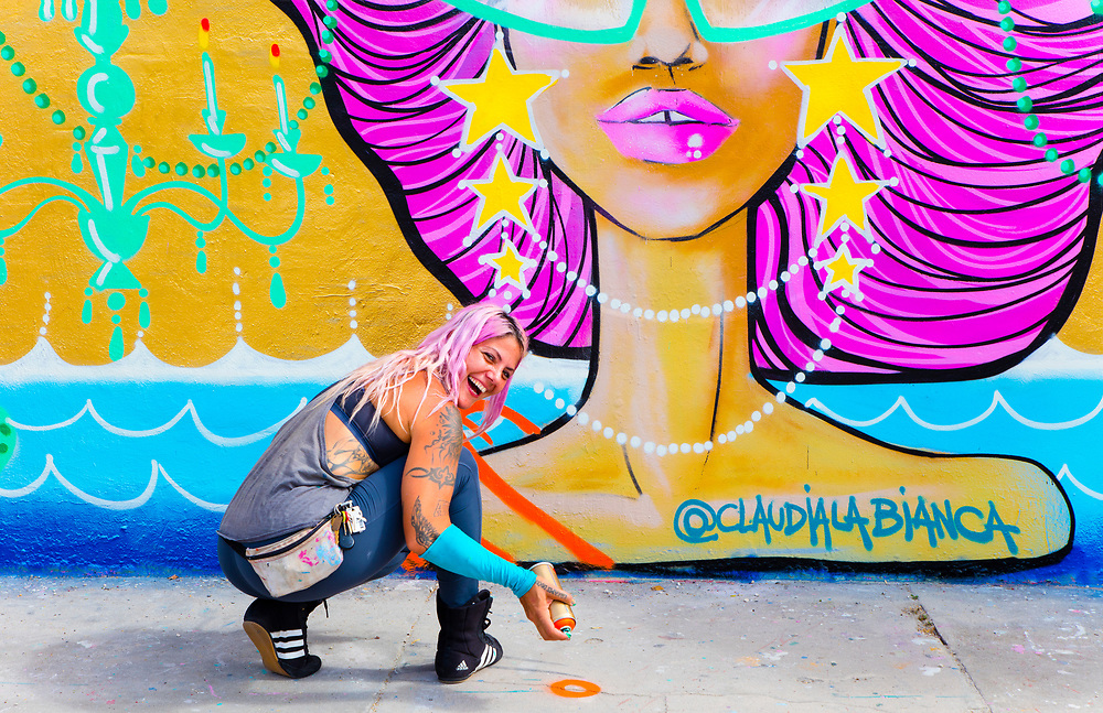Street artist Claudia LaBianca spray-painting a  mural at a vintage thrift store in Miami's high trending Wynwood neighborhood