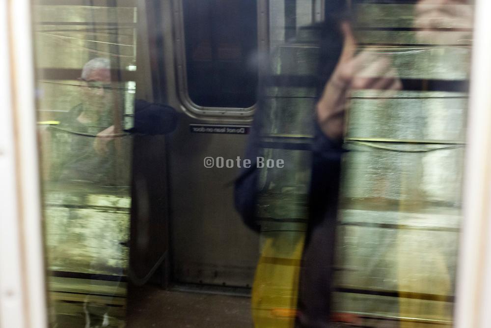 glass reflection with passenger New York subway