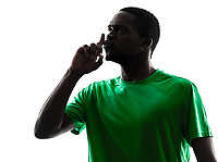 one african man soccer player hushing green jersey in silhouette on white background
