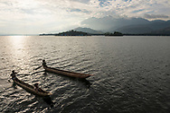 Lake Sentani, Papua, Indonesia - July 16, 2017: Young people in two dugout canoes paddle on Lake Sentani, located about 20 kilometers from the city of Jayapura in Papua, Indonesia.