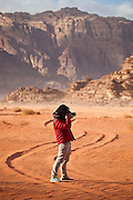 SeongRyeong Bak takes pictures along a Jeep track through the red sand desert of Wadi Rum, Jordan
