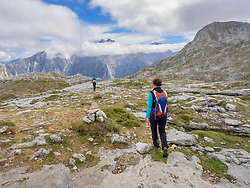 Woman and Man on  hiking tour in  Picos de Europa near Covadonga, Asturias, Northern Spain while In  background is summit of Picu Urriellu