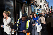 Street Scene with very different people on Piccadilly in London, England, United Kingdom. Here a street sweeper walks along with people who have been out shopping at the exclusive shops in the area.