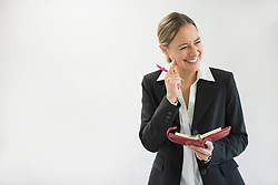Businesswoman in black suit holding notebook and pen, smiling